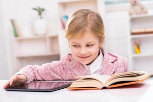 kleines Mädchen, das versucht, zwischen Buch und Tablet-Computer zu wählen foto