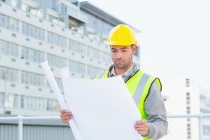Architekt liest Blaupause außerhalb des Gebäudes foto