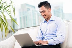 Geschäftsmann, der mit Laptop von zu Hause aus arbeitet foto