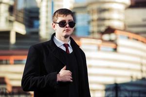 junger Geschäftsmann, der auf der Stadtstraße geht foto