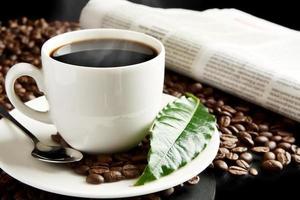 Tasse Kaffee mit Dunst mit Zeitung, Kaffeeblatt beim Frühstück foto
