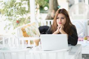 asiatische junge Geschäftsfrau, die im Café mit Laptop sitzt foto
