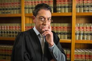 Anwalt, der Kamera in der Rechtsbibliothek betrachtet