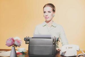 nachdenkliche Vintage 1950 blonde Sekretärin, die hinter Schreibtisch sitzt foto