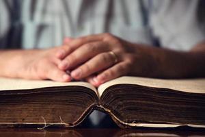 männliche Hand auf offener Bibel foto