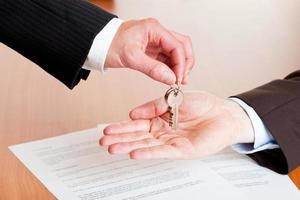 Geschäftsmann, der nach Vertragsunterzeichnung Hausschlüssel (Autoschlüssel) übergibt foto