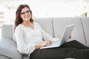 lächelnde Geschäftsfrau, die auf Sofa mit Laptop sitzt foto