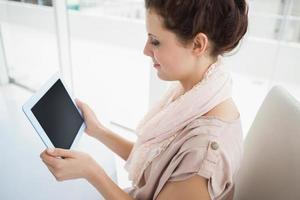 Gelegenheitsgeschäftsfrau, die digitales Tablett hält foto