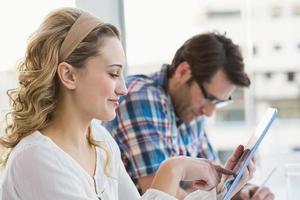 lächelnde lässige Blondine mit Tablette foto