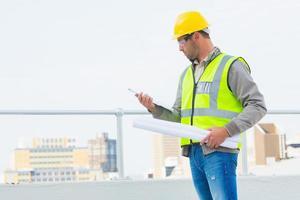 Architekt mit Blaupausen, die Zwischenablage im Freien lesen foto