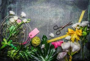 schöne Blumen, eine Schere und Werkzeuge, um Blumenstrauß zu schaffen