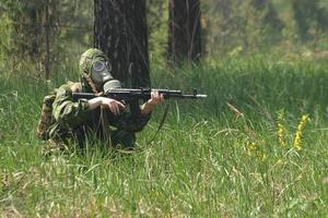 Soldat in Gasmaske mit Kalaschnikow foto