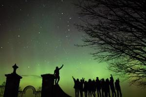 Nordlichter mit Sternschnuppe und Silhouetten (Aurora Borealis) foto