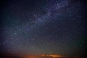 Sterne streuten sich durch den dunkelblauen Nachthimmel foto