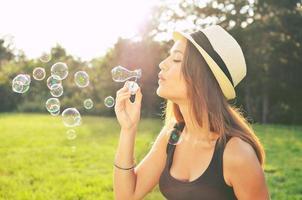 schöne Hipster-Frau, die Blasen bläst foto