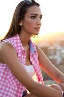 hübsches Mädchen, das auf dem Dach bei Sonnenuntergang sitzt. foto