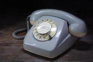 Retro-Telefon mit Drehknopf auf dunklem Holz foto