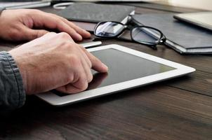 Mann klickt auf den Bildschirm des Tablets foto
