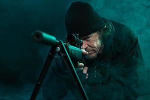 Scharfschütze mit Bart in schwarzer Haltepistole. Studioaufnahme.