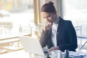 selbstbewusste Geschäftsfrau, die an einem Laptop arbeitet