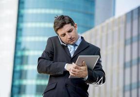 beschäftigter Geschäftsmann, der digitales Tablett und Handy im Freien überarbeitet hält foto