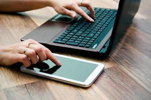 Frau, die mit Tablette und Laptop auf hölzernem Hintergrund arbeitet foto