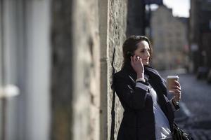 moderne Geschäftsfrau, die auf Handy draußen spricht. foto