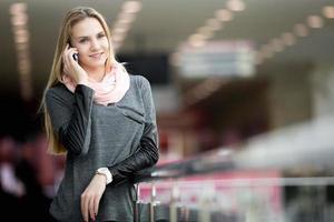 lächelnde Frau im zeitgenössischen großen Gebäude, das auf cellpho spricht