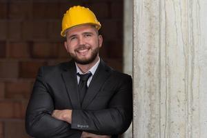 Porträt des glücklichen jungen Vorarbeiters mit Schutzhelm foto