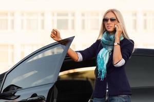 Modegeschäftsfrau, die am Telefon durch ihr Auto anruft foto