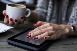 Frauenhand beim Stöbern auf dem Tablet