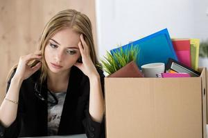 junge entlassene Arbeiterin, die in der Nähe des Kartons sitzt foto