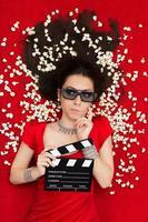 verwirrtes Mädchen mit 3D-Kinobrille, Popcorn und Regisseurschindel