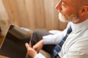 Geschäftsmann mittleren Alters, der von zu Hause aus mit einem Tablet arbeitet foto