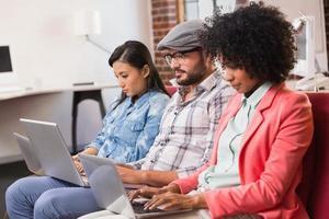 Gelegenheitskollegen mit Laptops auf der Couch foto