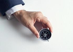 Geschäftsmann mit einem Kompass, der in der Hand auf Papierhintergrund hält foto