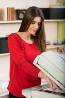hübsche junge Sekretärin mit einem Kopierer foto