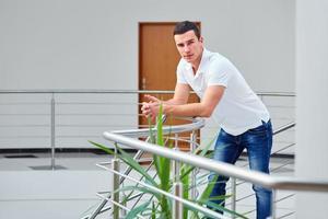 Mann in einem Poloshirt steht auf Geländer gelehnt foto