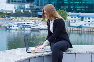 Geschäftsfrau, die auf Laptop auf dem Hintergrund der Wolkenkratzer arbeitet foto