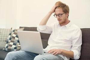junger Mann, der auf Couch mit Laptop sitzt