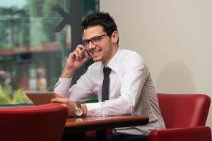 Geschäftsmann, der am Telefon spricht und Tablet verwendet foto
