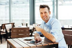 junger hübscher Mann mit einer Tasse Kaffee foto