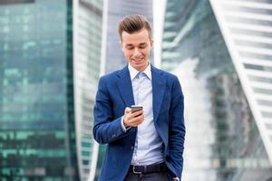 schöner Geschäftsmann im Anzug mit Smartphone in der Hand foto