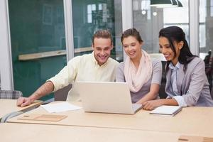 Drei glückliche Geschäftsleute, die zusammen an einem Laptop arbeiten foto