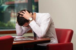 verzweifelter Manager, der Hände auf seinem Kopf hält foto