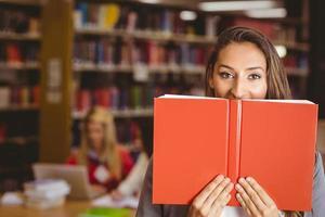 hübsche brünette Studentin, die Buch vor ihrem Gesicht hält foto