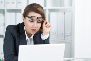 junge Geschäftsfrau, die Laptop genau betrachtet foto