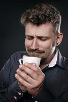 Mann in Bewunderung halten eine Tasse Kaffee in den Händen foto
