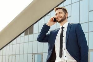 junger Geschäftsmann, der draußen auf seinem Telefon spricht foto
