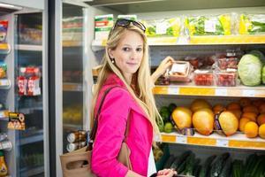 schöne junge Frau, die in einem Lebensmittelgeschäft einkauft foto